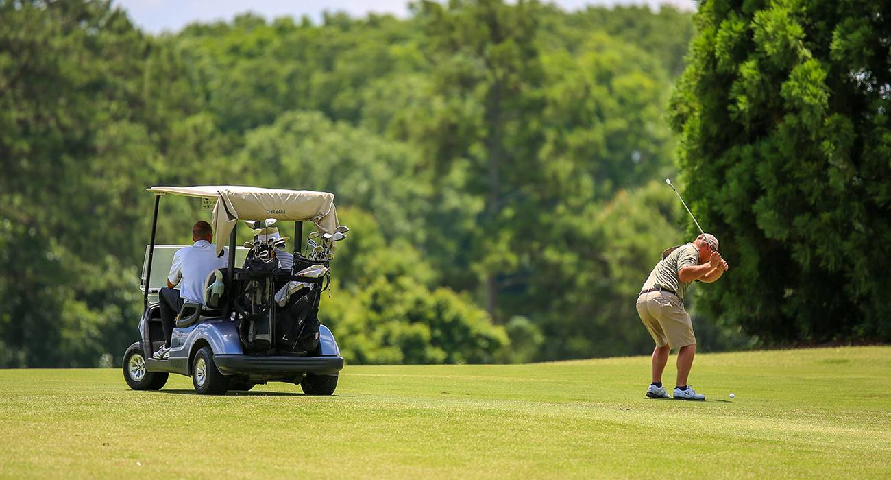 A man hits the ball while someone waits in the golf cart.